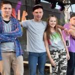 4 tancerzy pozuje do zdjęcia na scenie w plenerze. w tle budynki, na scenie napis: piknik na powitanie lata