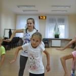 zdjęcie wykonane w sali. na zdjęciu grupa dzieci ucząca się układu choreograficznego