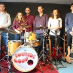 do zdjecia pozuje sześć młodych osób. muzyków. od lewej gitarzysta, skrzypaczka, prowadzacy zespół, perkusista, gitarzystka i basista. pozują w pomieszczeniu do prób.