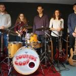 do zdjecia pozuje pięć młodych osób. muzyków. od lewej gitarzysta, skrzypaczka, perkusista, gitarzystka i basista. pozują w pomieszczeniu do prób.