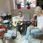 dwie dziewczynki w towarzystwie nauczycielki uczą się grać na gitarach. zdjecie wykonano w pomieszczeniu muzycznym. w tle stoi perkusja, ma regałach stoją bębny