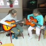 dwie dziewczynki uczą się grać na gitarach. zdjecie wykonano w pomieszczeniu muzycznym. w tle stoi perkusja, ma regałach stoją bębny