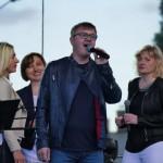 na pierwszym planie śpiewający mężczyzna, w tle trzy kobiety. koncert plenerowy.