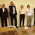 siedem elegancko ubranych osób - trzech mężczyzn i cztery kobiety śpiewaja na scenie w zaaranżowanym żłóbku. przed nimi leży sloma i mały żłóbeczek