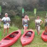 sześć osób - cztery kobiety i dwóch mężczyzn - roześmiani pozują do zdjecia na tle jeziora. na sobie maja kapoki, na trawie przed nimi leżą kajaki