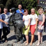 trzech mężczyzn i 4 kobiety w piękny, ciepły i słoneczny dzień pozują do zdjęcia przy figurze dudziarza.