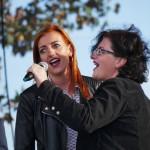 na zdjeciu dwie młode kobiety śpiewające do mikrofonu, który trzyma jedna z nich. za nimi błękitne niebo i zielone drzewa