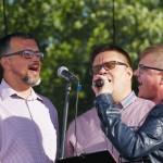 na zdjęciu trzech śpiewających mężczyzn. jeden z nich trzyma mikrofon, do którego wszyscy śpiewają. w tle zielone drzewa