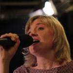 na pierwszym planie śpiewająca do mikrofonu blondynka