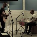 zdjęcie koncertowe. po lewej chłopak z gitarą, po prawej chłopak na perkusjonaliach. patrzą na siebie porozumiewawczo