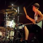 zdjecie koncertowe. perkusista przy srebrnej, mieniącej się w światłach perkusj. muzyk odwrócony jest od obiektywu