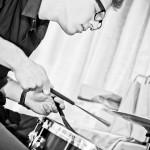 na pierwszym planie perkusista . zbliżenie na werbel. w rękach trzyma szczotki perkusyjne