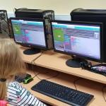 zdjęcie wykonane w pracowni komputerowej. siedzące tyłem do obiektywu dzieci pracują przy komputerach