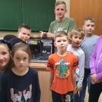 grupa uśmiechniętych dzieci pozuje do zdjęcia. stoją wokół biurka, na którym stoi komputer ze zdjętą obudową
