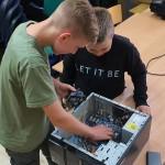 dwóch małych chłopców pochyla się nad komputerem stacjonarnym, z którego ściągnieto obudowę. przyglądają się jego podzespołom.