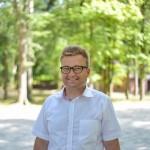 uśmiechnięty mężczyzna w okularach, w bialej koszuli z krótkim rękawem, stoi w słoneczny dzień na tle drzew w parku