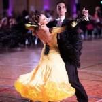 na pierwszym planie elegancko ubrana para taneczna. on w garniturze, ona w długiej żółtej sukni z odkrytymi plecami