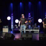 zdjęcie muzyków na scenie. od lewej gitarzysta, na podwyższeniu perkusista przy perkusji w złotym kolorze, wokalista w ciemnych okularach i czapce z daszkiem, oraz brodaty basista. na scenie białe i niebieskie światła
