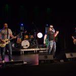 zdjęcie muzyków na scenie. od lewej gitarzysta, na podwyższeniu perkusista przy perkusji w złotym kolorze, wokalista w ciemnych okularach i czapce z daszkiem, oraz brodaty basista