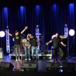 muzycy stoją na scenie, obejmują się.