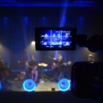 na pierwszym planie wizjer kamery w którym widać grających muzyków. tło dookoła rozmazane