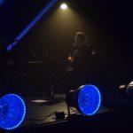 zbliżenie na gitarzystę. oświetlony jest jedną lampą i zlewa się z czarnym tłem. na pierwszym planie 3 niebieskie lampy
