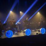 zdjecie z koncertu. meżczyzna na wiolonczeli, renata przemyk z małym bębnem, mężczyzna w koku na basie oraz gitarzysta. za nimi niebieskie światło, z przodu sceny 4 niebieskie lampy.