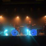 zdjecie z koncertu. meżczyzna na wiolonczeli, renata przemyk z małym bębnem, męzczyzna w koku na basie oraz gitarzysta. za nimi białe światło, z przodu sceny 4 niebieskie lampy.