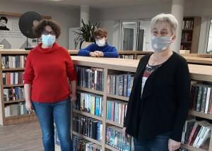 zdjęcie wykonane w pomieszczeniu bibliotecznym. do zdjecia pozują stojące przy regałach z książkami 3 bibliotekarki w maskach na twarzach