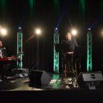 scena, w tle na wysokich słupach delikatne białe światła. na scenie 3 muzyków. centralnie, na barowym stołu siedzi bard, marek dyjak, po lewej pianista, po prawej trębacz