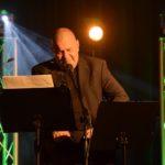 zdjęcie z koncertu, na scenie ciepłe światło. na pierwszym planie siedzący, zamyślony marek dyjak, łysy mężczyzna, w czarnym garniturze i koszulce