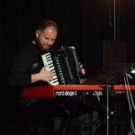 zdjecie z koncertu. za czerwonym pianinem siedzi brodaty muzyk i gra na akordeonie