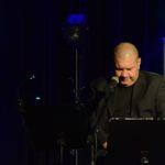 zdjęcie z koncertu, na scenie błękitne i białe światło. na pierwszym planie siedzący, zamyślony marek dyjak, łysy mężczyzna, w czarnym garniturze i koszulce