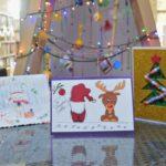 na stoliku stoją 3 kartki świąteczne. w tle drabina przystrojona jak choinka