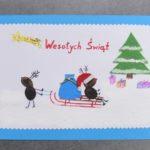 kartka świąteczna, dookoła niebieska ramka w środku biały prostokąt. czerwony napis wesołych świąt i kometa. po prawej stronie zielona choinka z prezentami, po lewej renifer ciagnie na sankach innego renifera