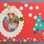 kartka świąteczna. czerwone tło. po lewej stronie kartki świeta rodzina. dookoła złote gwiazdki i napis wesołych świąt. po prawej papierowa choinka i białe śnieżynki