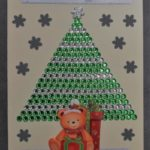 kartka świąteczna z trójkątną choinką z wielu, ciasno przyklejonych cekinów. dookoła choinki srebrne płatki śnieg przed choinką siedzi miś. na górze i na dole kartki elegancki napis wesołych świat