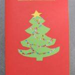czerwona kartka świąteczna. na środku wycięta z papieru choinka, na niej łańcuchy z małych cekinów i papierowa gwiazdka. nad choinką napis marry christmass