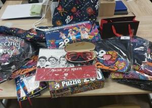 na zdjeciu blat stołu na którym rozłożono gadżety 29 finału wośp. poduszka w kształcie serca, kalendarze, notatniki, koszulki, puzzle, charakterystyczne, czerwone okulary i torby.