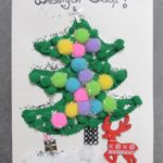 Kartka świąteczna, na białym tle choinka z małych pluszowych kulek. pod nią renifer i prezenty. na górze napis wesołych świat