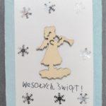 kartka świąteczna, na środku drewniany aniołek - gotowy element. dookoła naklejone brokatowe śnieżynki. pod aniołem niezgrabny dziecięcy napis: wesołych świąt