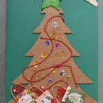 kartka świateczna. na zielonym tle kartonowa choinka ozdobiona cekinami i sznurkami. pod choinką małe prezenty
