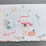 karka świąteczna wycięta ozdobnym cięciem. ręcznie rysowana. niedźwiadek w mikołajowej czapce stoi w lesie trzymając prezent. po lewej stronie u dołu napis wesołych świąt