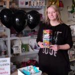 zdjecie wykonane w sklepie papierniczym. na tle unoszących się czarnych balonów i regałów z artykułami papierniczymi i reklamowymi pozuje ubrana na czarno kobieta. trzyma przed sobą puszkę 29 finału wośp.