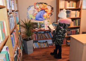 Zdjecie wykonane w pomieszczeniu bibliotecznym. na pierwszym planie obrócona tyłem do obiektywu dziewczynka w zimowym ubraniu czyta książkę. dookoła nije stoją regały z książkami
