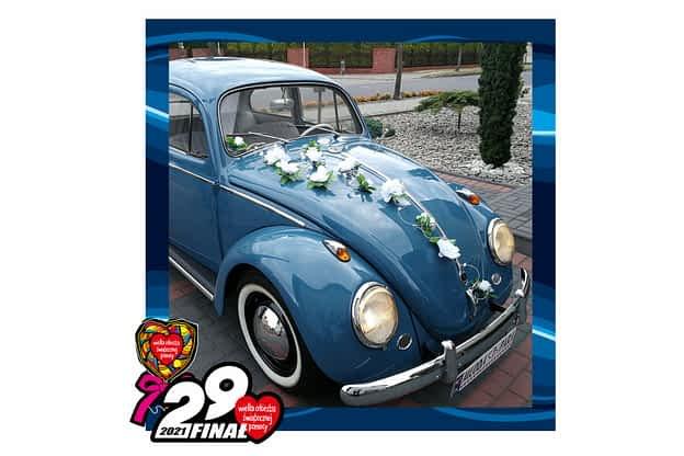 na zdjęciu w niebieskiej ramce 29 finału wośp stary, odpicowany błękitny volkswagen garbus przystrojony kwiatami