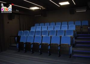 pusta widownia sali kinowej. niebieskie fotele i czarne ściany. w lewym górnym rogu logotyp kina za rogiem