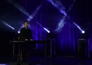 zdjęcie z koncertu, na scenie błękitne, krzyżujące się światła oraz dymy. na środku sceny jedyny muzyk, pianista i piosenkarz mateusz ziółko siedzący przy pianinie