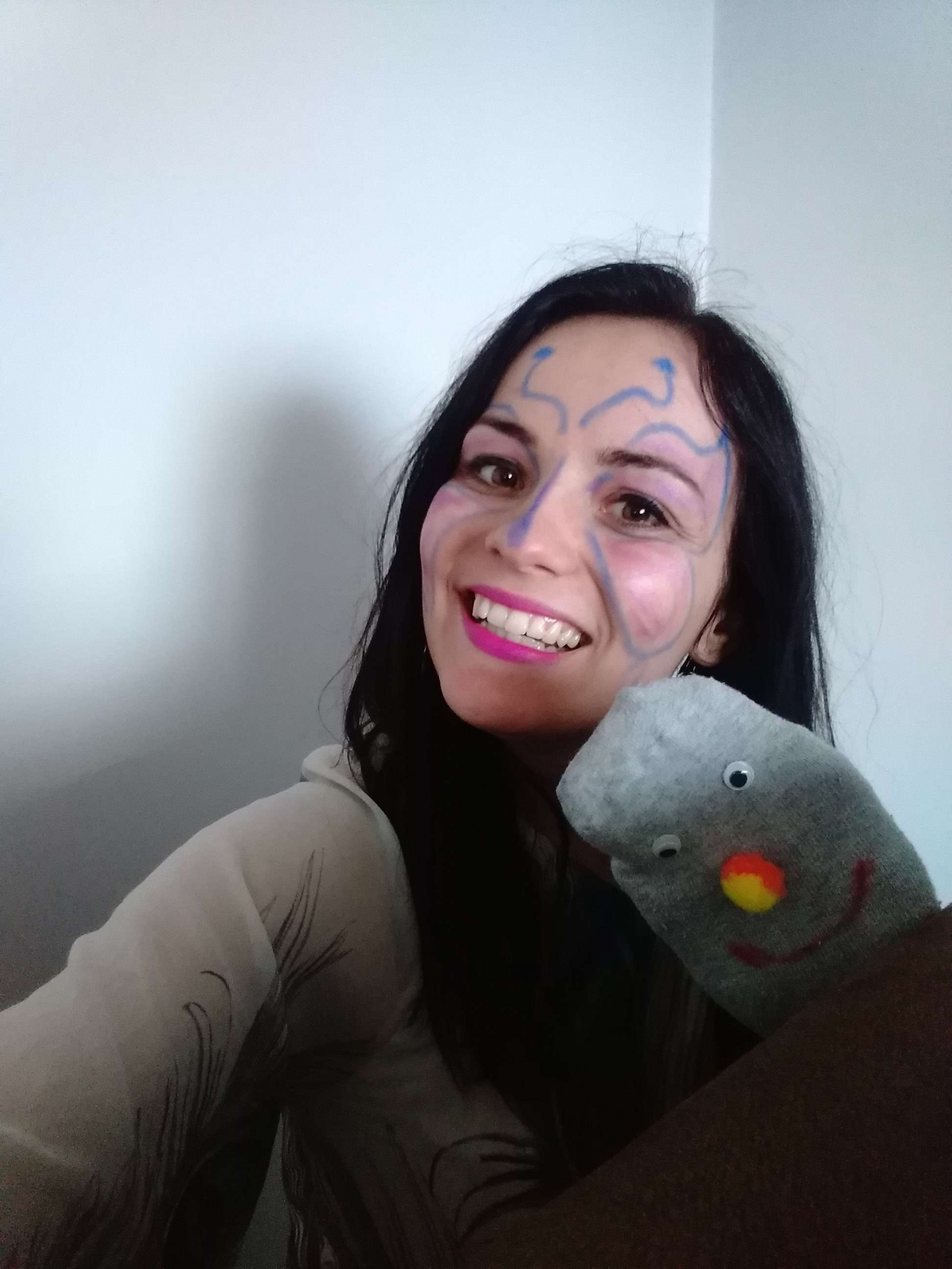 NA zdjęciu uśmiechnięta czarnowłosa kobieta. Ma na twarzy namalowane kolorowe wzorki. W ręce ma pacynkę ze skarpetki