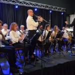 Zdjecie z koncertu. Niebieskie światła. Orkiestra na scenie. dyrygent odwrócony plecami. W pierwszym rzędzie stoi klarnecista i gra solo.